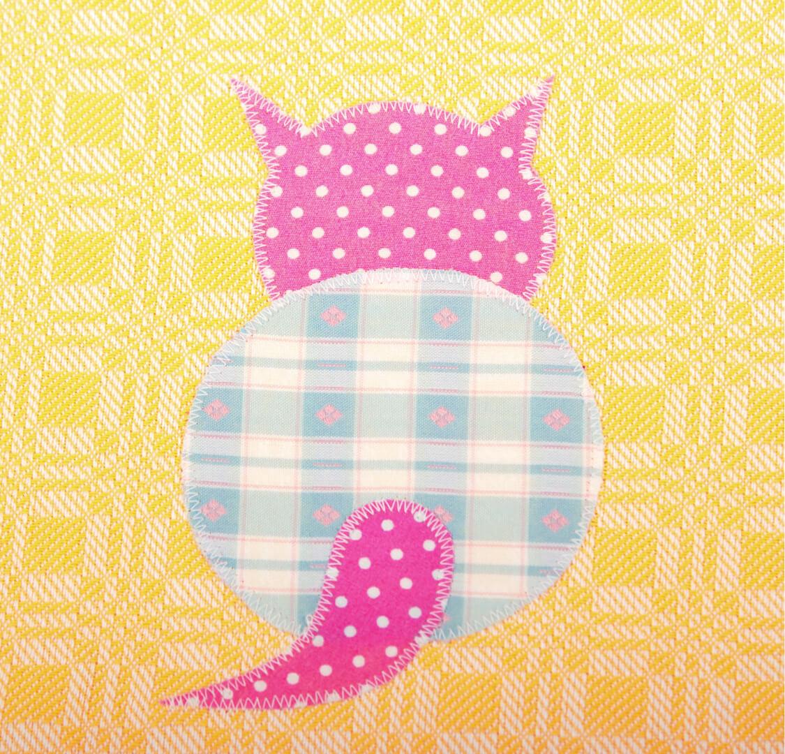 Gelbes Geschirrtuch mit sitzender rosa Katze