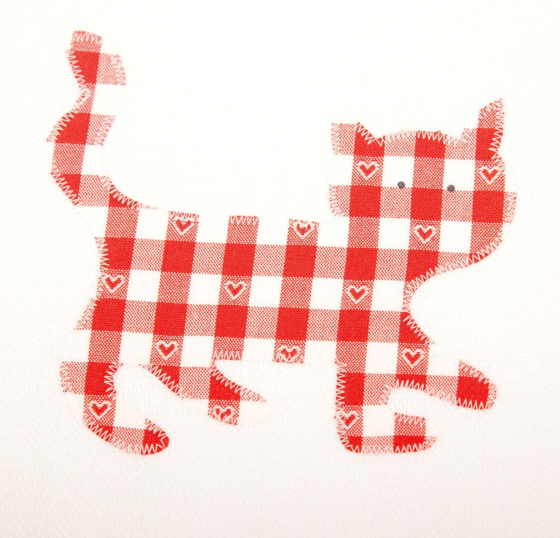 Weißes Geschirrtuch mit laufender roter Katze