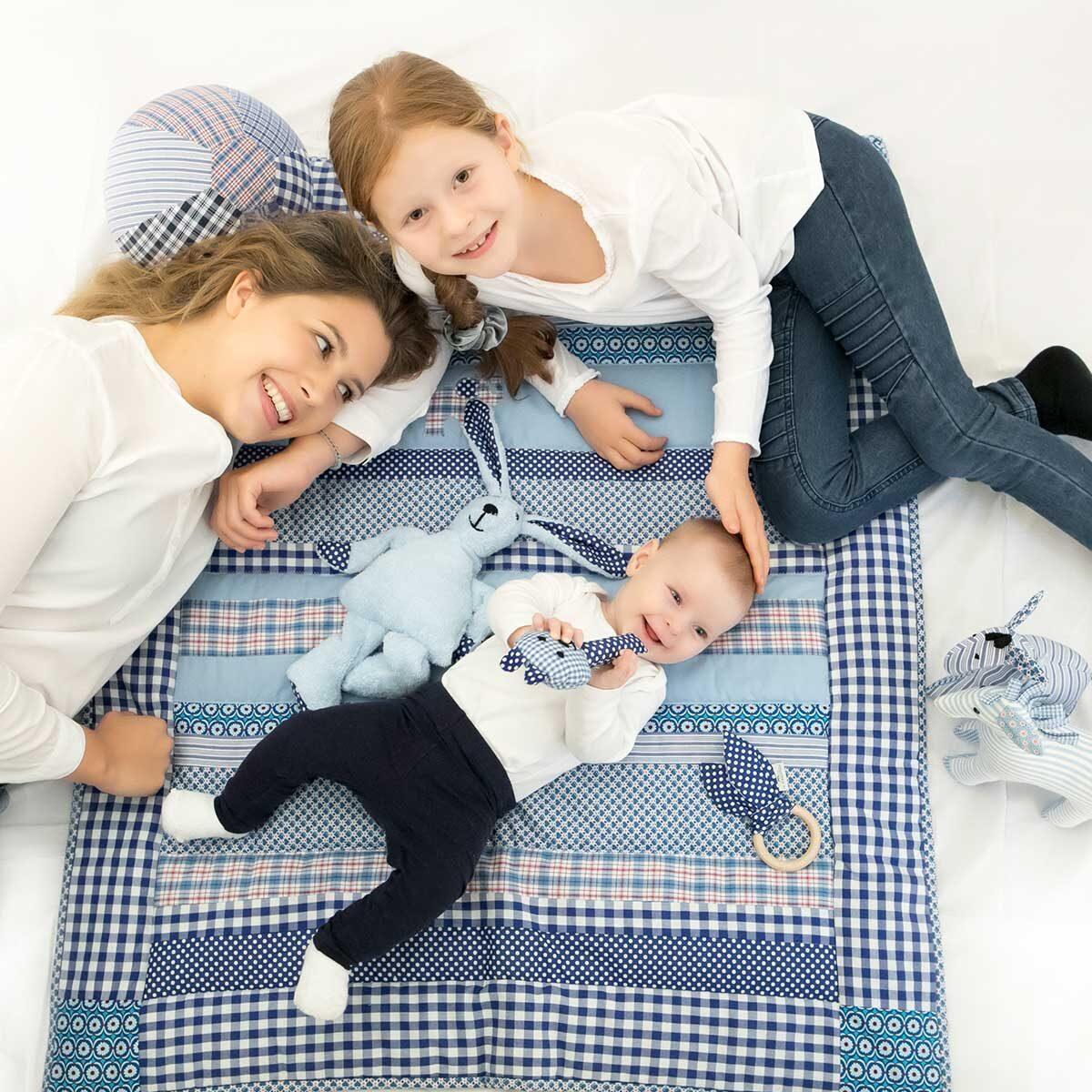 Baby auf Decke und Kinder